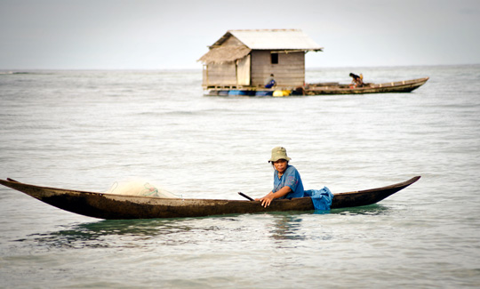 Mentawai woman fishing in a small dugout canoe