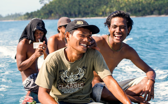 Mentawai youth in a dugout canoe, laughing