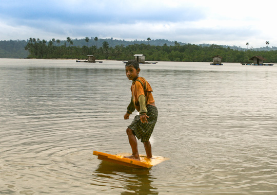 Young Mentawai boy practicing surfing on an old plastic door