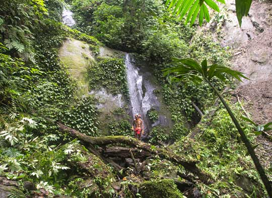 Sikerei standing by a large waterfall in the Mentawai rainforest